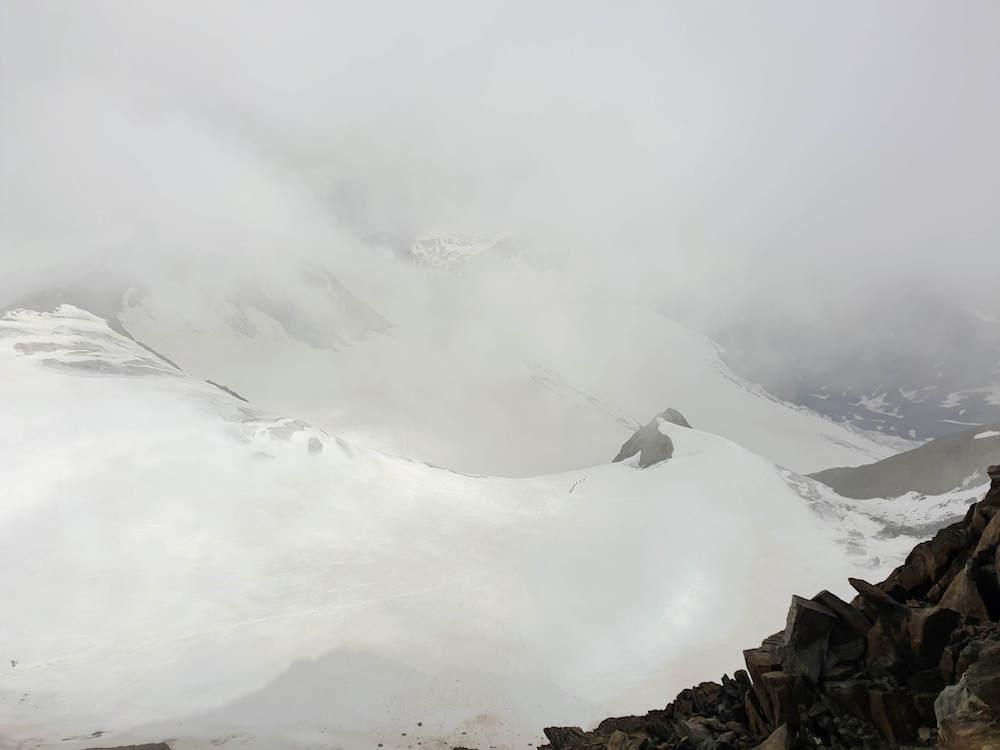 Glimps van het uitzicht vanaf de Wildspitze tussen de wolken door