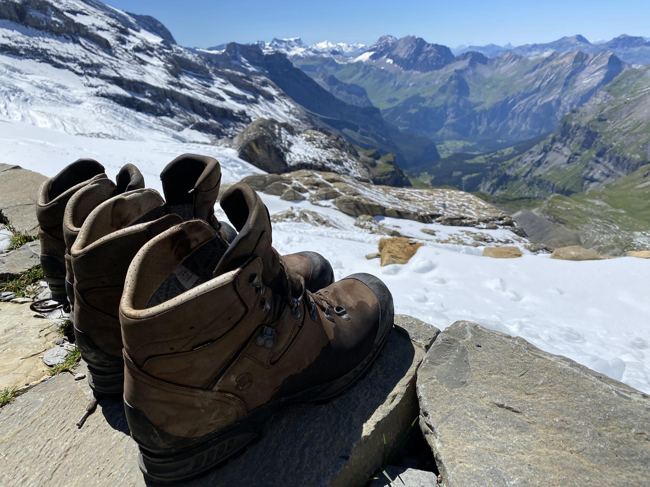 Schoenen staan op de rand van het terras met de bergen op de achtergrond